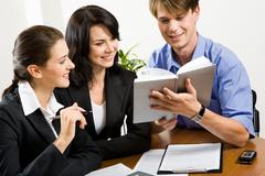 portrait of three  professionals looking at male's notepad - stock photo