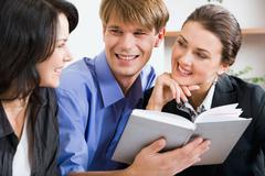 business man holding the notepad between two women - stock photo