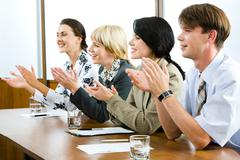 Successful applauding young people sitting at the table in the office Stock Photos