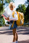 First-former girl is going to school carrying backpack and holding a book Stock Photos