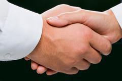 close-up of shaking hands on the black background - stock photo