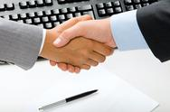 Stock Photo of woman and man shaking hands over blank paper and pen, keyboard on the background