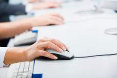 Row of hands touching computer mice lying on the table Stock Photos