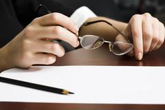 Sheet of paper and pencil on the desk and human hands holding glasses Stock Photos