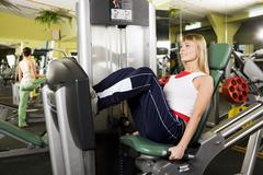 Photo of sporty woman in gym sitting on special training apparatus and looking f Stock Photos