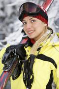 sporting young beautiful woman with skies on the background of snow-covered fore - stock photo