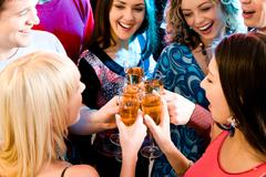 Group of champagne flutes in people's hands making a toast Stock Photos
