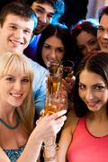 Stock Photo of image of smiling friends holding alcoholic drinks and looking at camera