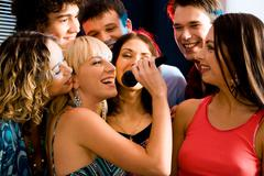 Pretty woman sings a song in the environment of her friends at a karaoke party Stock Photos