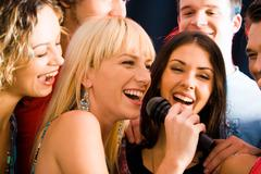 Portrait of three young attractive women singing together Stock Photos