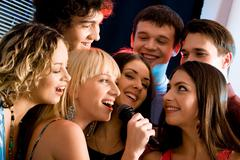 attractive woman is holding the microphone and singing with friends - stock photo