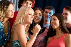 Portrait of seven young attractive friends at a karaoke party Stock Photos