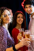 Three people are holding the glasses of champagne and looking at camera Stock Photos