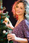 beautiful woman touching the ball on the christmas-tree - stock photo