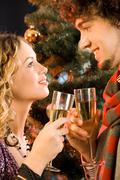 Portrait of amorous couple holding the glasses of champagne at christmas Stock Photos