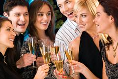 Portrait of six happy people holding glasses of champagne making a toast Stock Photos
