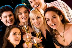 Stock Photo of portrait of several friends raising up their glasses