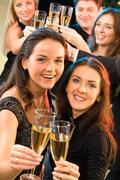 portrait of  young women raising up their bocals of champagne - stock photo