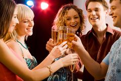 portrait of five happy people holding glasses of champagne making a toast - stock photo