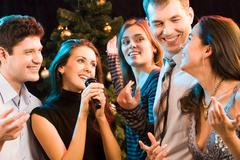 portrait of five friends having fun at karaoke party - stock photo