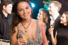 Portrait of charming woman holding her cocktail on the background of people Stock Photos
