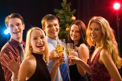 Smiling group of young people enjoying cocktails at christmas Stock Photos