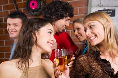 Stock Photo of happy women gazing on the each other and holding the cocktails