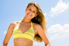 Portrait of happy woman in a yellow bikini on a background of sky Stock Photos