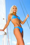 Image of pretty woman standing on a deck of yacht Stock Photos