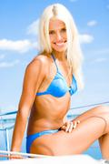 Bright photo of blonde woman in blue bikini on a background of sky Stock Photos
