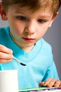 portrait of smart little boy drawing a picture - stock photo