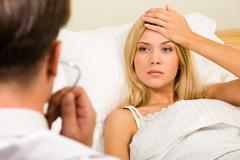 Image of pretty woman in bed touching her forehead and looking at doctor Stock Photos