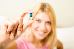 close-up of woman's hand holding pill between thumb and forefinger - stock photo