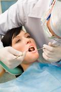 Image of young lady with dentist over her checking oral cavity Stock Photos