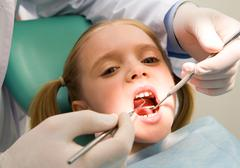 photo of small girl looking at camera with open mouth while it being examined by - stock photo