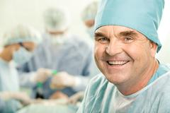 Portrait of senior doctor smiling on the background of his colleagues Stock Photos
