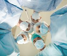 view of doctors by patient after operation on background of lamp and ceiling - stock photo