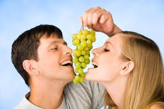 portrait of man and young woman eating bunch of grapes - stock photo