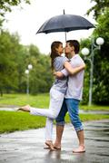 Photo of romantic barefooted couple standing on the road in rain and going to ki Stock Photos