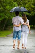 rear backs of couple embracing each other in the park - stock photo