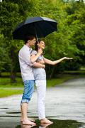 portrait of man hugging happy woman under umbrella - stock photo