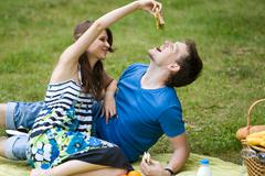 Photo of amorous couple having lunch at picnic while happy girl holding sandwich Stock Photos