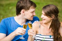 photo of two happy people drinking wine and looking at each other with smiles - stock photo