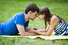 Photo of pretty girl and handsome guy lying on green grass in front of each othe Stock Photos