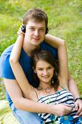 Portrait of happy guy holding his girlfriend on knees while both wearing headpho Stock Photos