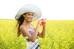 Photo of young woman wearing hat holding photo camera on meadow in summer Stock Photos