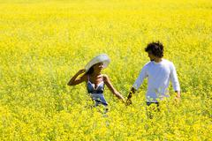 Image of amorous couple walking in yellow meadow holding by hands and looking at Stock Photos