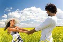Photo of attractive couple holding by hands and whirling on the meadow at leisur Stock Photos