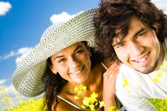 close-up of handsome guy and pretty girl looking at camera with smiles at summer - stock photo