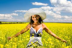 Portrait of pretty woman standing in the middle of yellow meadow and looking at Stock Photos